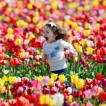 girl running in tulip field, children's happiness
